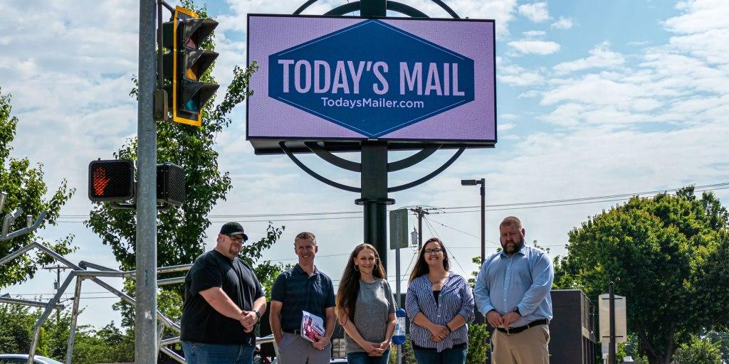 Today's Mail team standing under digital billboard sign